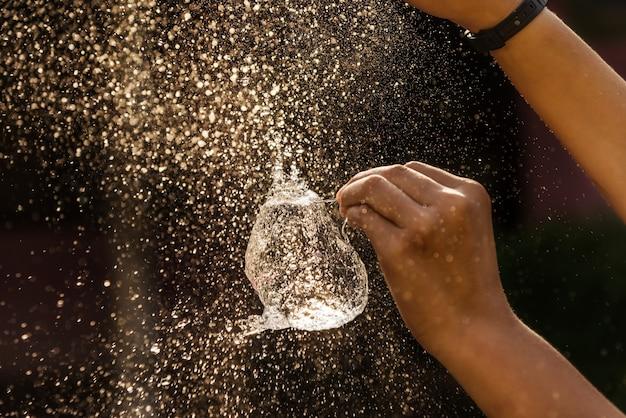 Main de fille avec des éclaboussures d'eau sur fond noir Photo Premium