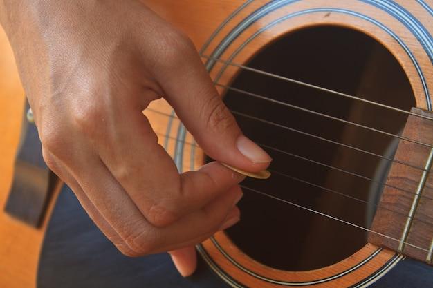 Main de fille jouant de la guitare acoustique Photo Premium