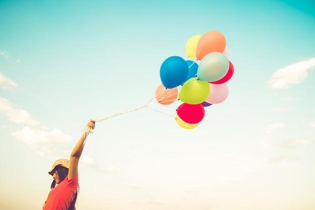 Main de fille tenant des ballons multicolores Photo Premium