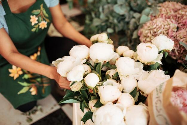 Main de fleuriste femelle arrangeant des fleurs de pivoine blanches Photo gratuit