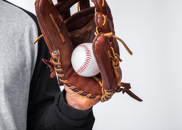 Main avec un gant tenant une balle de baseball Photo gratuit
