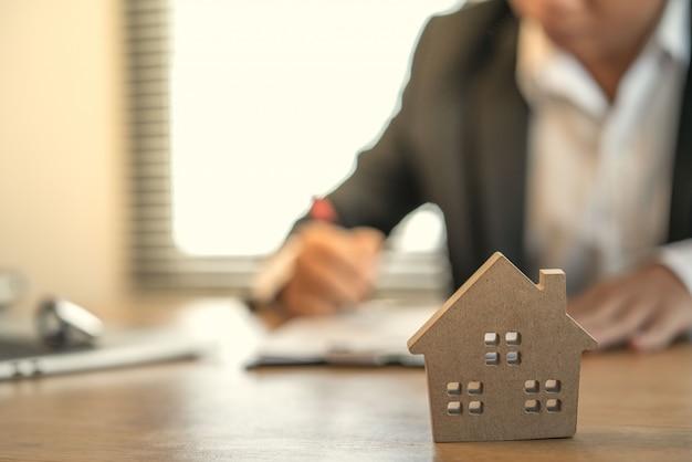 Main de gens d'affaires calculant les intérêts, les taxes et les bénéfices à investir dans l'immobilier et l'achat d'une maison Photo Premium
