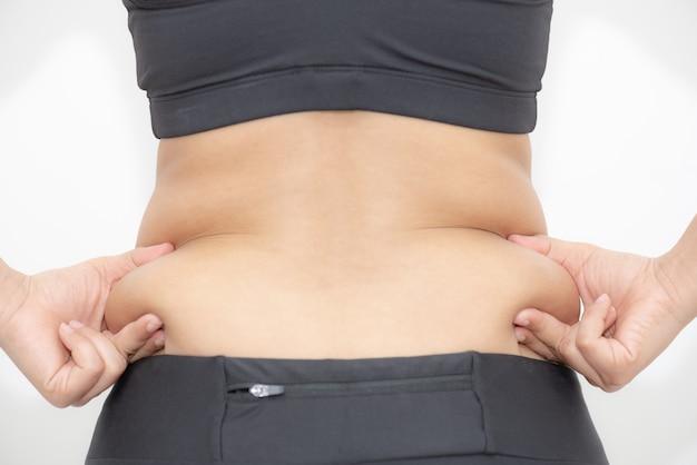 Main de grosse femme tenant la graisse du ventre excessive sur fond blanc. Photo Premium
