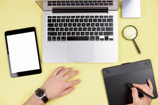 Main d'homme d'affaires à l'aide de tablette numérique graphique avec ordinateur portable et tablette numérique sur fond jaune Photo gratuit