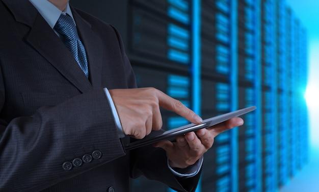 Main d'homme d'affaires à l'aide d'une tablette et de la salle des serveurs Photo Premium