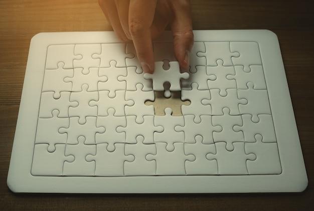 Main d'homme d'affaires détenant des puzzles de dernière pièce, concept de succès commercial Photo Premium