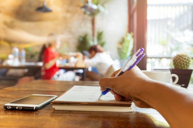 Main d'homme d'affaires écrit calendrier dans l'agenda du calendrier avec un stylo sur la table. Photo Premium