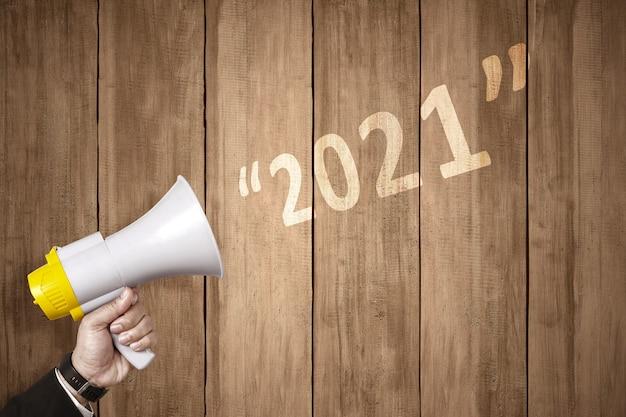 La Main D'homme D'affaires Avec Un Mégaphone Annonce La Bonne Année. Bonne Année 2021 Photo Premium