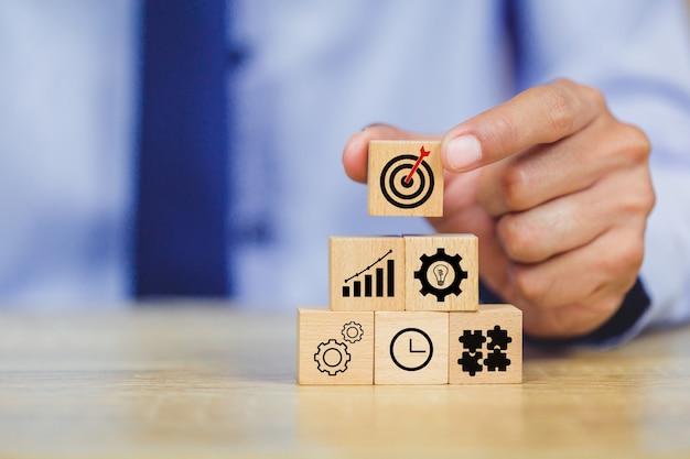 Main d'homme d'affaires mettant le bloc de bois sur le dessus avec le concept de réussite cible. Photo Premium