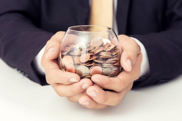 Main d'homme d'affaires mettant les pièces sur le verre, concept d'économiser de l'argent pour la comptabilité financière Photo Premium