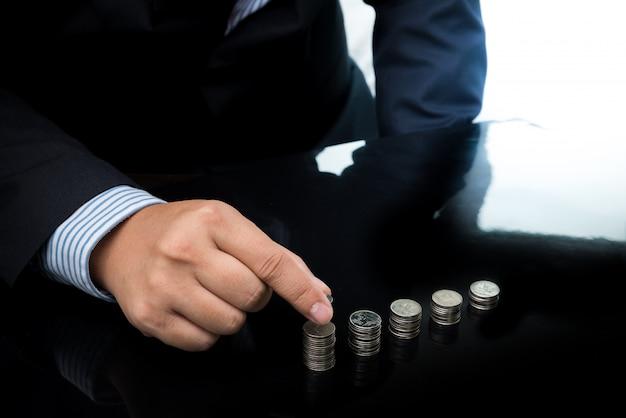 Main d'homme d'affaires mettre des pièces de monnaie pour empiler des pièces de monnaie Photo Premium