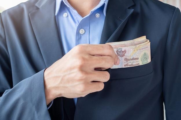 Main d'homme d'affaires sur la pile de billets de baht thaïlandais. Photo Premium