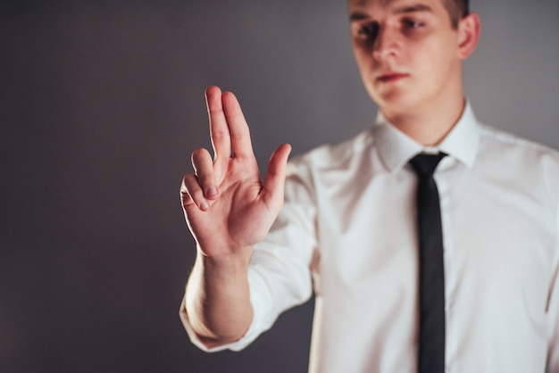 Main d'homme d'affaires pointant dans l'espace vide sur fond noir Photo Premium