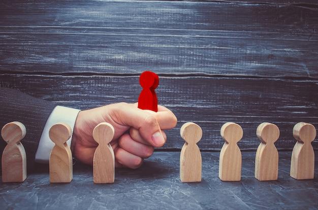 Main d'un homme d'affaires prend une figure en bois rouge d'un homme. le concept de recherche Photo Premium