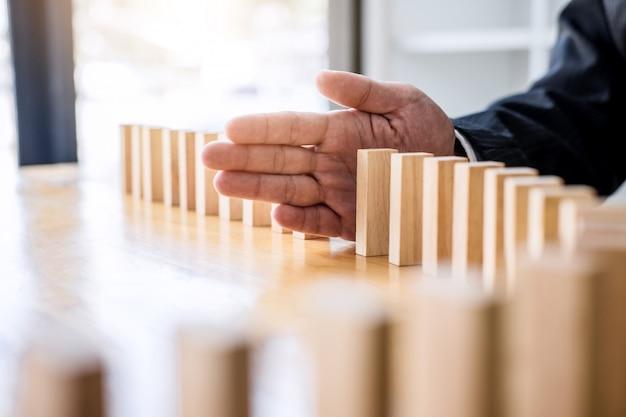 Main d'homme d'affaires s'arrêtant en baisse effet de dominos en bois Photo Premium