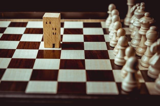 Main d'homme d'affaires se déplaçant d'échecs au bâtiment et aux modèles de maison dans le jeu d'échecs Photo Premium