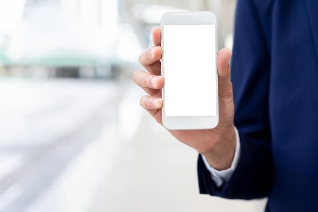 Main d'homme d'affaires sur smartphone avec écran blanc Photo Premium