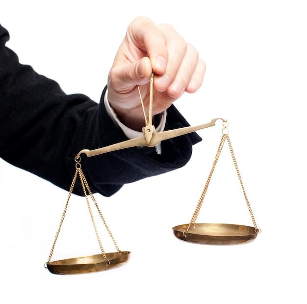 Main d'homme d'affaires tenant une balance Photo Premium