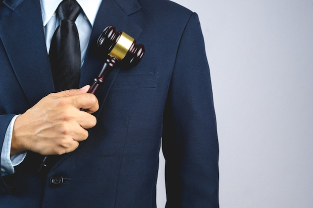 Main d'homme d'affaires tenant le marteau du juge en bois comme un signe de loi ou de justice Photo Premium