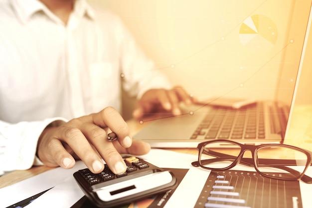 Main de l'homme d'affaires travaillant avec ordinateur portable sur le conseiller en investissement de bureau bureau en bois. Photo Premium
