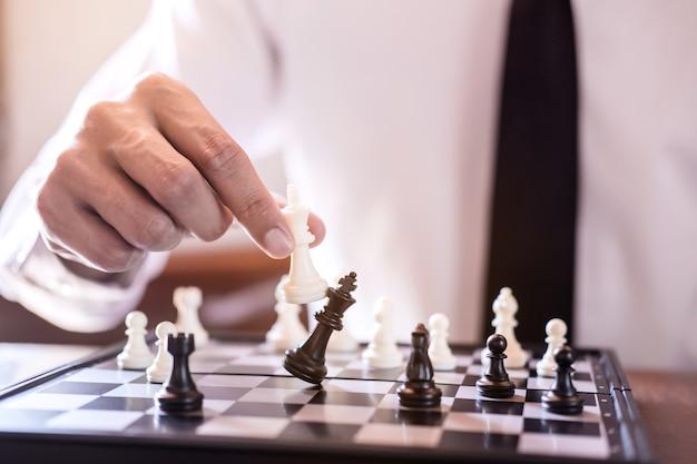 Main D'homme D'affaires Utiliser Roi Pièce D'échecs Blanc Jeu De Jeu Pour Renverser Renverser L'opposition Photo Premium