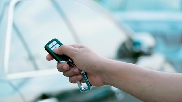 La main de l'homme appuie sur les systèmes d'alarme de la voiture télécommandée. Photo Premium