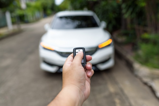 La main d'un homme appuie sur la télécommande pour verrouiller ou déverrouiller la portière de la voiture. Photo Premium