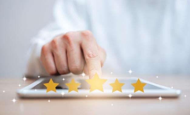 Main d'homme en appuyant sur l'écran de la tablette numérique avec or cinq étoiles classement Photo Premium