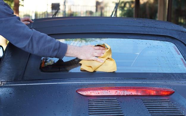 La main de l'homme closeup lave une voiture. main tient l'éponge pour laver la voiture Photo Premium