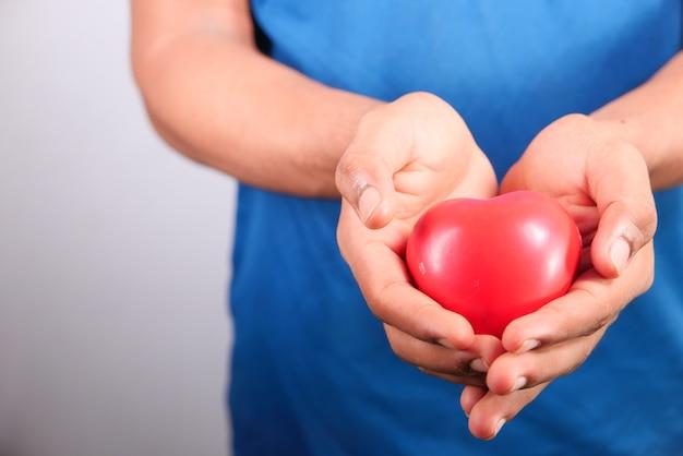 Main De L'homme Avec Coeur Sur Fond Blanc. Fermer. Photo Premium