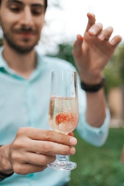 Main De L'homme Déposer Une Fraise Dans Un Verre Avec Du Vin Mousseux. Belle Vie, Cellebration Photo gratuit