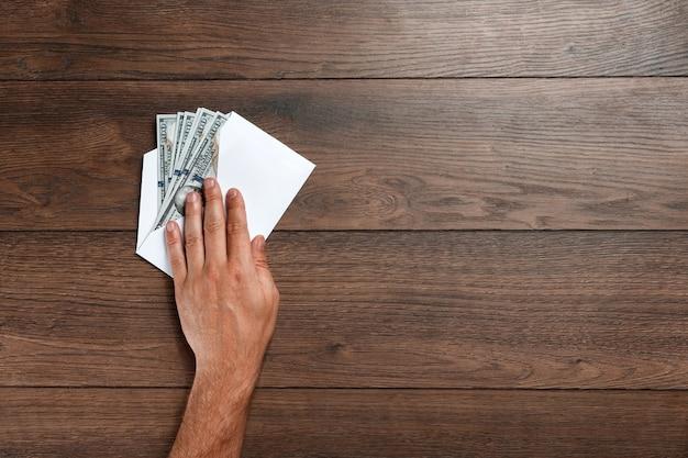 La main de l'homme et les dollars des états-unis dans une enveloppe blanche Photo Premium