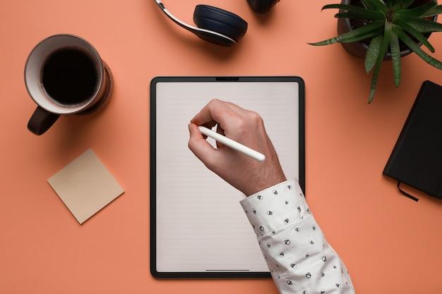 La Main D'un Homme écrit Des Notes Dans Une Tablette Numérique Maquette Photo Premium
