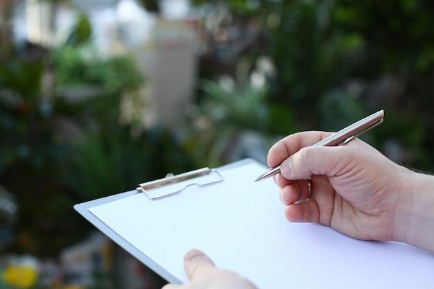 Main De L'homme écrit Sur Le Presse-papiers Avec Du Papier Blanc. Photo Premium