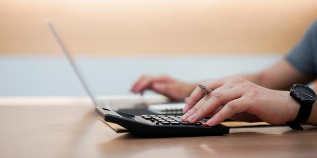 Main d'homme employé comptable en appuyant sur la calculatrice et en tapant le clavier sur un ordinateur portable Photo Premium