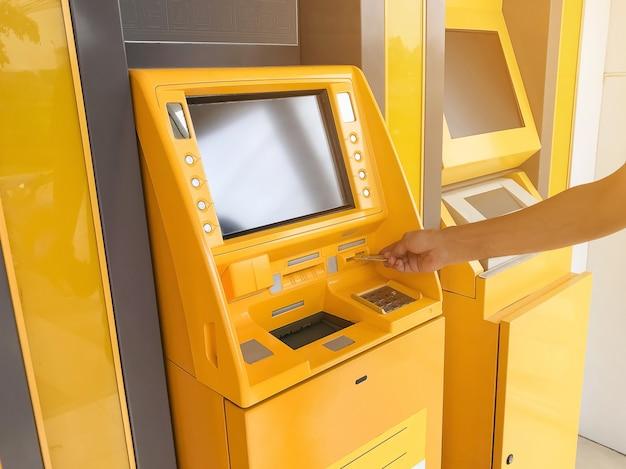 La main de l'homme insère une carte de guichet automatique dans un guichet automatique bancaire. Photo Premium