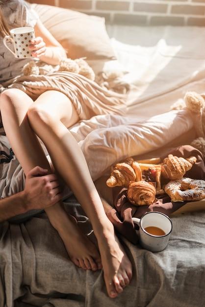 La main de l'homme sur la jambe de la femme assise sur le lit avec un petit déjeuner cuit et une tasse de café Photo gratuit