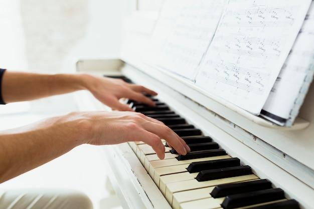 Main d'homme jouant du piano avec des notes de musique Photo gratuit