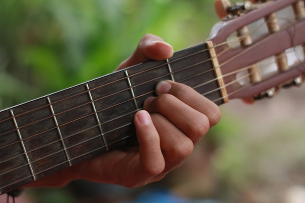 La main d'un homme jouant de la guitare et de la musique Photo Premium