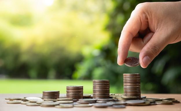 La main de l'homme met des pièces d'argent pour empiler des pièces Photo Premium