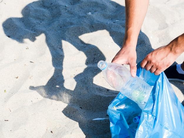 Main de l'homme mettant une bouteille d'eau vide dans un sac à ordures bleu sur le sable Photo gratuit