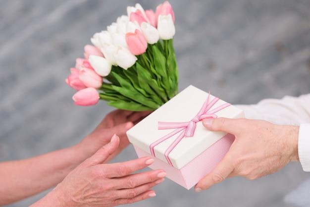 Main de l'homme offrant un bouquet de fleurs et de cadeau d'anniversaire à sa femme Photo gratuit