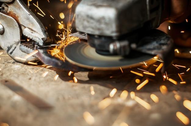 Main de l'homme avec l'outil de coupe en acier flou sur fond noir Photo Premium