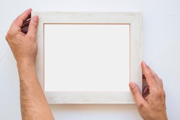 Main de l'homme plaçant le cadre photo blanc sur le mur Photo gratuit