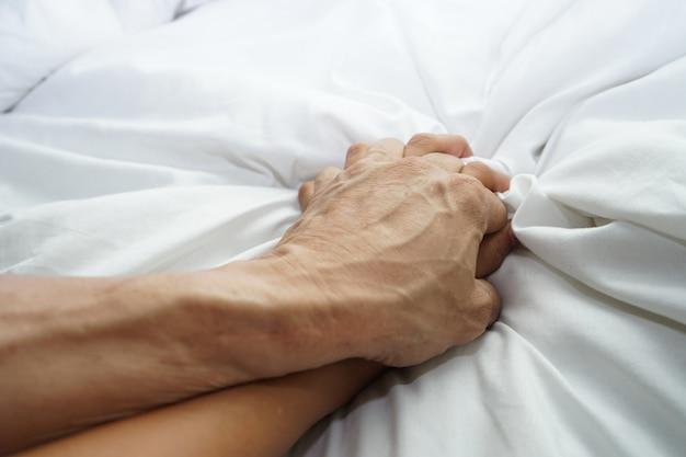 Main d'un homme poilu tenant une main de femme pour concept de viol et d'abus sexuel Photo Premium