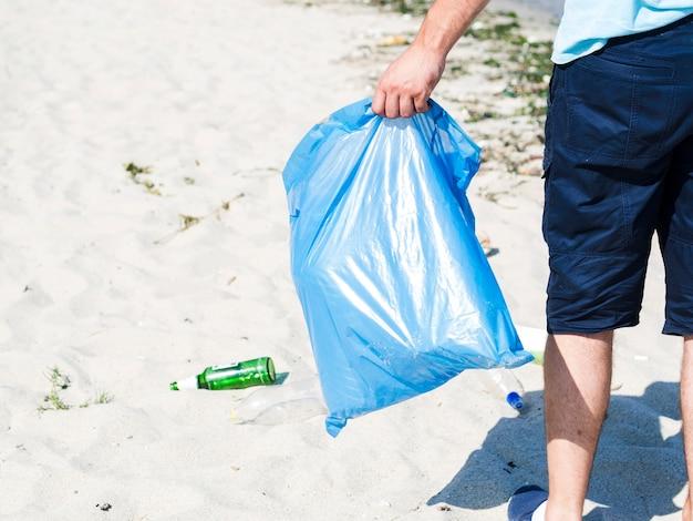 Main d'homme portant un sac poubelle bleu sur la plage Photo gratuit