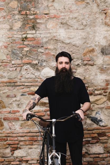 Main de l'homme avec tatouage sur le siège du vélo contre le mur patiné Photo gratuit