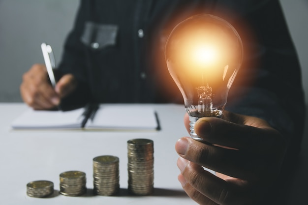 Main d'homme tenant une ampoule avec une pile de pièces pour la comptabilité et le concept créatif. Photo Premium