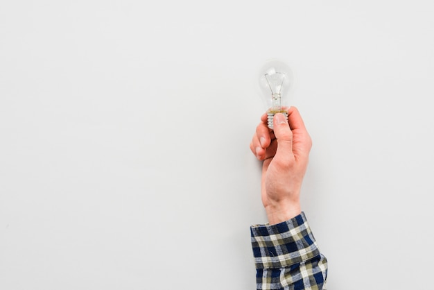 Main d'homme tenant l'ampoule Photo gratuit