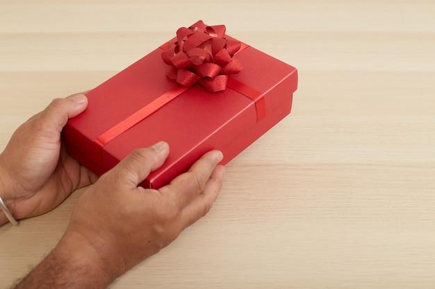 Main D'homme Tenant Une Boîte-cadeau Rouge Photo Premium